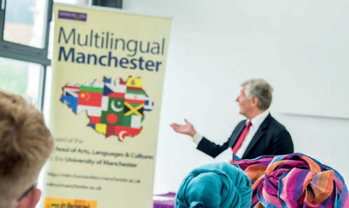 Multilingual Manchester talk in front of a pull-up banner