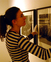 Museology student hanging photographs with white gloves