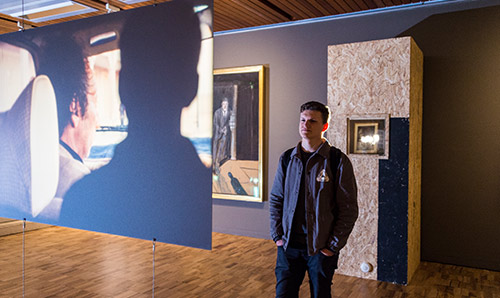 Man looking at artwork in gallery