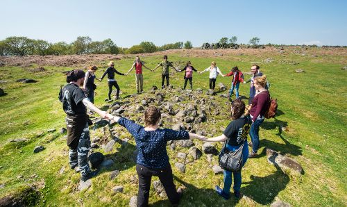 Archaeology group on a field trip holding hands in a circle.