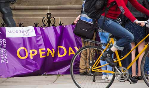 Cyclist going past open days sign