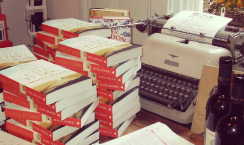 Pile of books on a desk with a typewriter