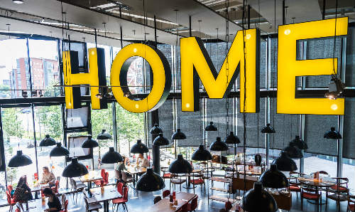 Big yellow letter sign hanging from ceiling in cafe that spells home