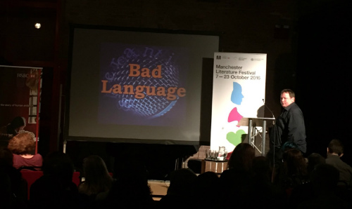 Event with people sat down and man on stage with Bad Language logo in the background