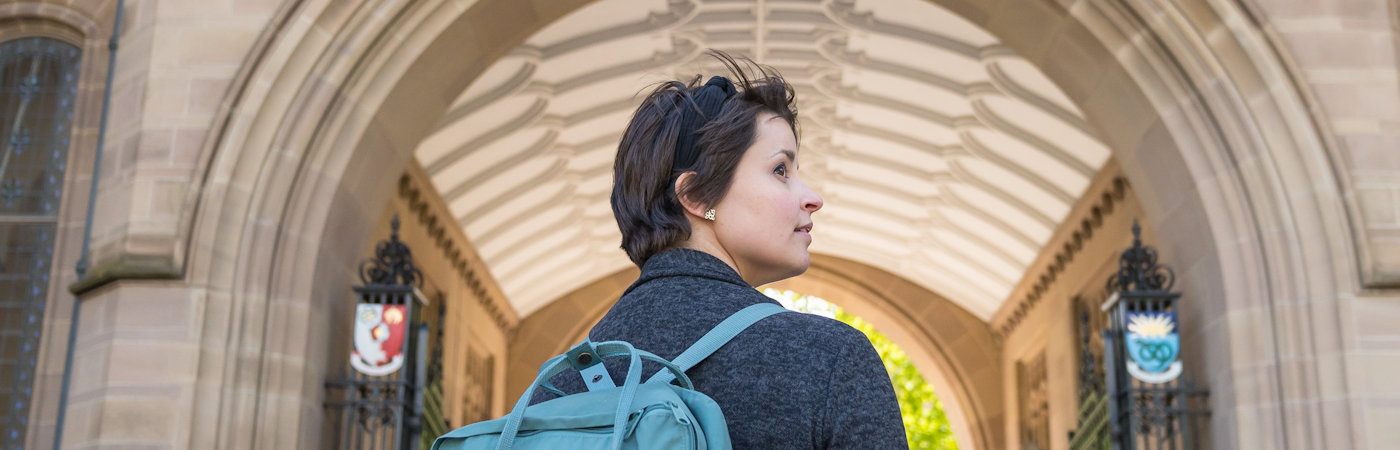 Student walking under arch of Whitworth Hall.