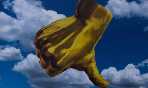 Drawing of golden thumb in the sky