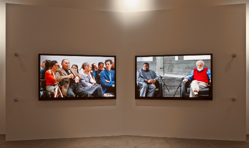 Wall installation with two flat screen tvs showing a film