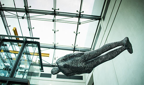 Anthony Gormley sculpture hanging from a glass ceiling in Manchester Art Gallery