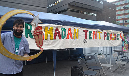 Man in front of Ramadan Tent project sign