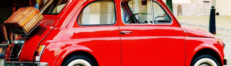 An image of a classic bright red Fiat 500