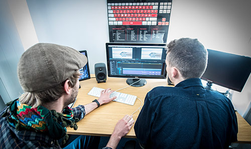 Two male students sat in front of media editing equipment