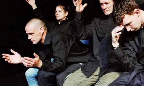 Four performers in black shirts gesturing with their hands out