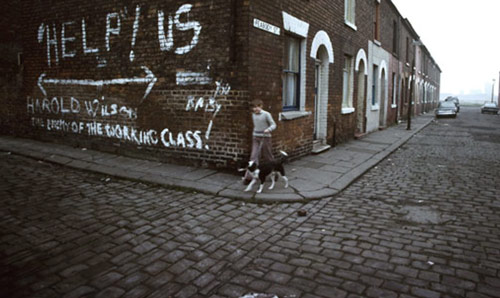 Boy walking a dog in 1980s Manchester on terraced street