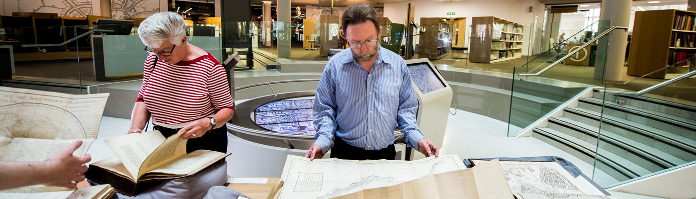 Members of research staff reading old maps in the library