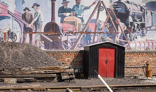 Painted scene of the history of transport on a brick wall next to train track