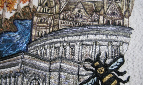embroidery of a bee flying over a town