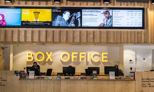 Sign on wall in yellow that says box office