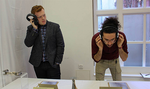 Two male students listening to an audio piece in the Healing Histories exhibition with headphones