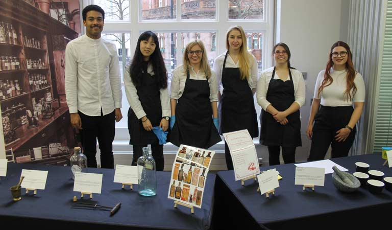 Students with pharmacy exhibitions which included a pestle and mortar, medicine bottles and an antique set of forceps.