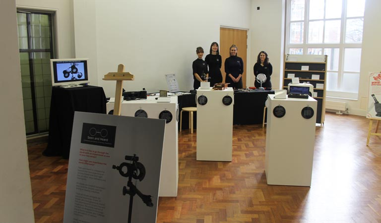 Photograph of the exhibition space and four students.