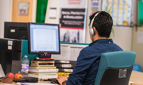 Man sat at desk on computer with headphones on