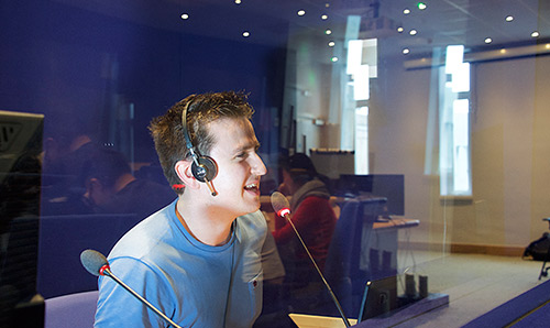 Man wearing headphones talking into microphone in a studio
