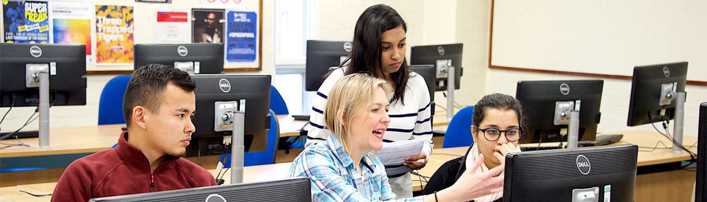 Female teaching students at a computer