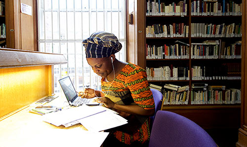 Woman working at desk in library
