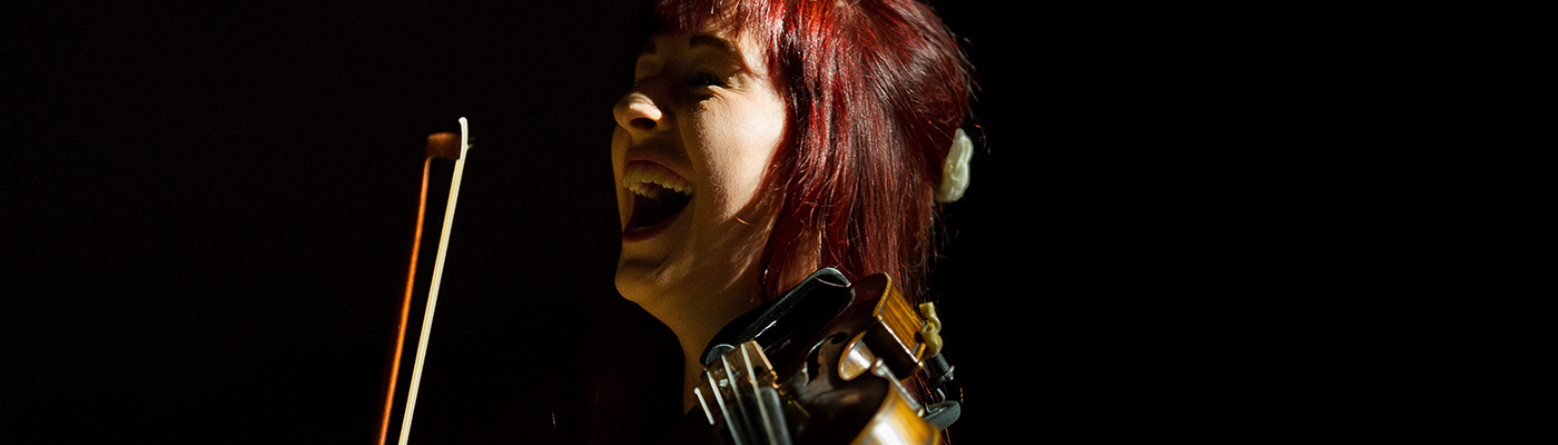 Female student playing the violin and laughing.