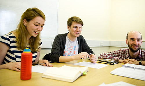 Three students sat at table laughing