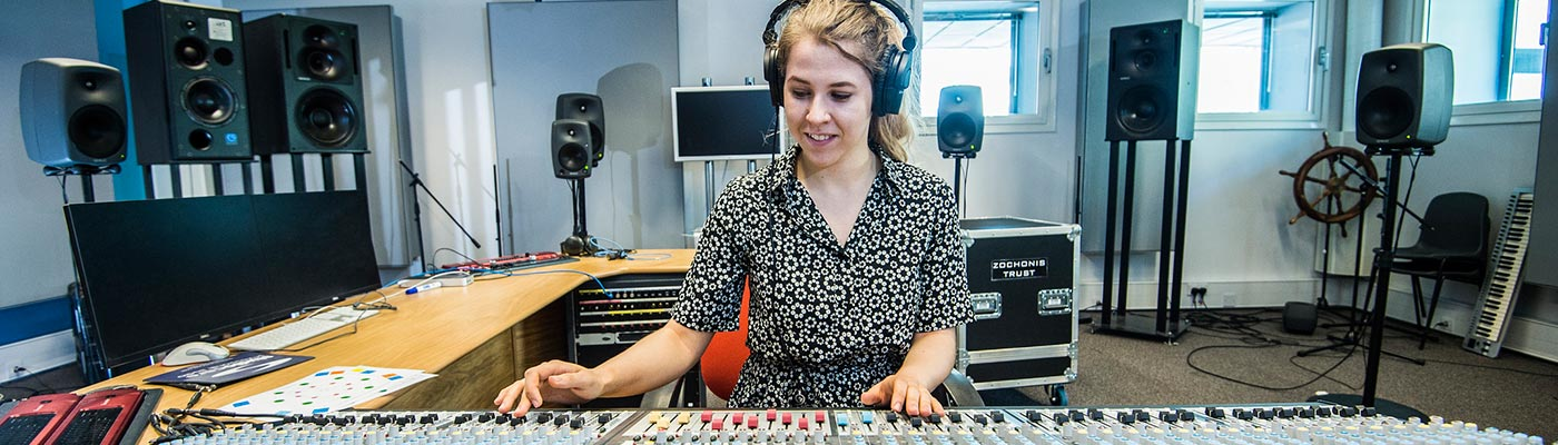 Female student at a mixing desk in the electroacoustic building