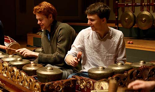Two male students playing percussion instruments and smiling.