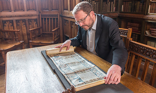 Researcher examining scroll