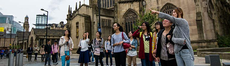 Students pointing by Manchester Cathedral