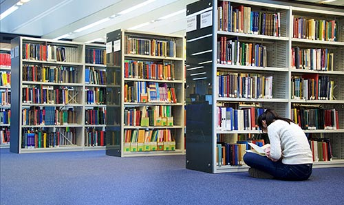 Female sat on the floor in library reading a book